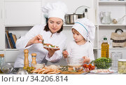 Купить «Girl and her mother are cooking vegetables dish together in the kitchen», фото № 34206814, снято 27 января 2018 г. (c) Яков Филимонов / Фотобанк Лори