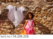 Girl in Halloween costume by stone wall with ghost. Стоковое фото, фотограф Сергей Новиков / Фотобанк Лори