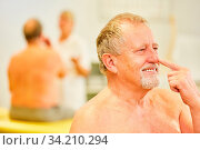 Senior Mann mit dem Zeigefinger an der Nase beim Finger-Nase-Versuch beim Hausarzt. Стоковое фото, фотограф Zoonar.com/Robert Kneschke / age Fotostock / Фотобанк Лори