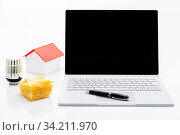Das Foto zeigt einen silbernen Laptop und Haus mit Thermostat und Dämmwolle isoliert auf weißem Hintergrund. Стоковое фото, фотограф Zoonar.com/Ralf Kalytta / easy Fotostock / Фотобанк Лори