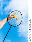 Female hand strikes yellow shuttlecock by badminton racquet with background from blue sky with white clouds in sunny day (focus on the shuttlecock) Стоковое фото, фотограф Zoonar.com/Valery Voennyy / easy Fotostock / Фотобанк Лори