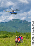 Group of women travelers watching flight of tourist helicopter in sky on background mountains, green forest, clouds in summer sunny weather (2014 год). Редакционное фото, фотограф А. А. Пирагис / Фотобанк Лори