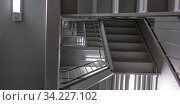 Купить «Indoor stairs and ceiling of a modern building. View from below a high stairway inside a modern building with numerous floors. Bright rectangular lights can be seen on the ceiling of each landing.», фото № 34227102, снято 16 июля 2020 г. (c) easy Fotostock / Фотобанк Лори