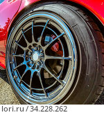 Купить «Red car with silver rim on its wheels. Close up shot of a clean wheel with shiny silver rim. The car has a reflective bright red paint that gleams under the sunlight.», фото № 34228262, снято 4 августа 2020 г. (c) easy Fotostock / Фотобанк Лори
