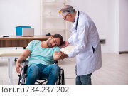 Experienced doctor and young male patient in wheel-chair. Стоковое фото, фотограф Elnur / Фотобанк Лори
