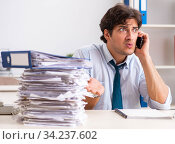 Overloaded busy employee with too much work and paperwork. Стоковое фото, фотограф Elnur / Фотобанк Лори