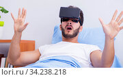 Patient in the hospital with VR glasses headset. Стоковое фото, фотограф Elnur / Фотобанк Лори