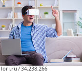 Freelance student with virtual reality glasses at home. Стоковое фото, фотограф Elnur / Фотобанк Лори