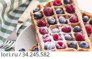 Купить «Belgian waffles on plate with berries», видеоролик № 34245582, снято 8 июля 2020 г. (c) Сергей Петерман / Фотобанк Лори