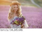 pretty blonde woman running away in lavender field. woman in long dress and straw hat having fun in flowers of lavender. Стоковое фото, фотограф Юрий Голяк / Фотобанк Лори