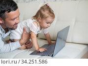 Little girl and caring father are watching cartoons on a laptop while lying on the couch at home. A man shows his little daughter photographs on a computer. Beloved daddy. Стоковое фото, фотограф Михаил Решетников / Фотобанк Лори