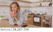 Beautiful woman drinking coffee in the kitchen. Стоковое видео, агентство Wavebreak Media / Фотобанк Лори