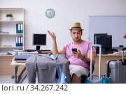 Купить «Young male employee preparing for the trip», фото № 34267242, снято 28 мая 2020 г. (c) Elnur / Фотобанк Лори