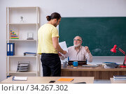 Old teacher and young male student in the classroom. Стоковое фото, фотограф Elnur / Фотобанк Лори