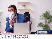 Купить «Male employee with mask in hipocrisy concept», фото № 34267762, снято 13 декабря 2019 г. (c) Elnur / Фотобанк Лори