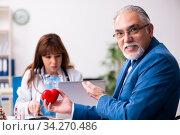 Old businessman visiting young female doctor. Стоковое фото, фотограф Elnur / Фотобанк Лори