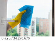 Washing glass of home window in urban apartment house by blue rag. Стоковое фото, фотограф Zoonar.com/Valery Voennyy / easy Fotostock / Фотобанк Лори