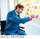 Young handsome man in wheelchair with many conflicting prioritie. Стоковое фото, фотограф Elnur / Фотобанк Лори