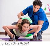 Купить «Fitness instructor helping sportsman during exercise», фото № 34276074, снято 10 июля 2018 г. (c) Elnur / Фотобанк Лори