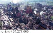 Купить «Дым и вредные выбросы из труб металлургической домны. Полет над индустриальной зоной», видеоролик № 34277666, снято 29 мая 2020 г. (c) Евгений Ткачёв / Фотобанк Лори