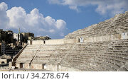 Roman Theatre against the background of moving clouds in Amman, Jordan -- theatre was built the reign of Antonius Pius (138-161 CE), the large and steeply raked structure could seat about 6000 people. Стоковое видео, видеограф Владимир Журавлев / Фотобанк Лори