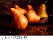 Golden Pear on Wooden Table and Few Pears on Backdrop. Стоковое фото, фотограф Zoonar.com/Vsevolod Belousov / easy Fotostock / Фотобанк Лори