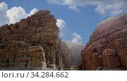 Купить «Rocks Wadi Mujib against the background of moving clouds -- national park located in area of Dead sea, Jordan», видеоролик № 34284662, снято 3 августа 2020 г. (c) Владимир Журавлев / Фотобанк Лори
