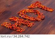 Inscription from dry cayenne pepper on wooden surface. Стоковое фото, фотограф Яков Филимонов / Фотобанк Лори