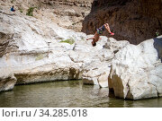 Sporty guy doing backflip off cliff into lake in an oasis in middle of Oman desert. Стоковое фото, фотограф Matej Kastelic / Фотобанк Лори