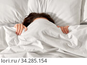woman lying in bed under white blanket or duvet. Стоковое фото, фотограф Syda Productions / Фотобанк Лори