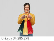 Купить «happy smiling young woman with shopping bags», фото № 34285278, снято 20 марта 2020 г. (c) Syda Productions / Фотобанк Лори