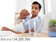 man in bed dropping medicine into glass of water. Стоковое фото, фотограф Syda Productions / Фотобанк Лори