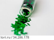 green glitters poured from small glass bottle. Стоковое фото, фотограф Syda Productions / Фотобанк Лори