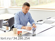 architect with blueprint working at home office. Стоковое фото, фотограф Syda Productions / Фотобанк Лори