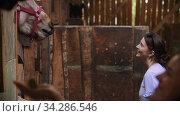 Two young women feeding carrots horses in paddock. Стоковое видео, видеограф Константин Шишкин / Фотобанк Лори