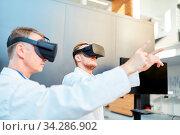 Wissenschaftler trainieren mit der Virtual Reality Brille für die Medizin Forschung. Стоковое фото, фотограф Zoonar.com/Robert Kneschke / age Fotostock / Фотобанк Лори