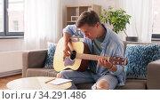 Купить «young man playing guitar at home», видеоролик № 34291486, снято 10 июля 2020 г. (c) Syda Productions / Фотобанк Лори