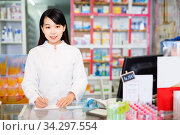 Chinese woman pharmacist keeps track of drugs in interior of pharmacy. Стоковое фото, фотограф Яков Филимонов / Фотобанк Лори