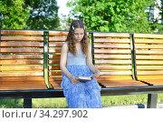 Thoughtful Girl reading a book while sitting on the bench. Стоковое фото, фотограф Бражников Андрей / Фотобанк Лори
