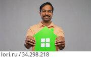 smiling indian man holding green house icon. Стоковое видео, видеограф Syda Productions / Фотобанк Лори