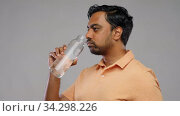 happy indian man drinking water from glass bottle. Стоковое видео, видеограф Syda Productions / Фотобанк Лори
