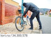 Vermummter Dieb klaut ein Fahrrad in einer Stadt. Стоковое фото, фотограф Zoonar.com/Robert Kneschke / age Fotostock / Фотобанк Лори