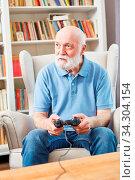 Senior Mann spielt Videospiel mit Konsole im Wohnzimmer als Beschäftigung. Стоковое фото, фотограф Zoonar.com/Robert Kneschke / age Fotostock / Фотобанк Лори