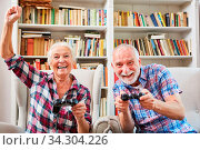 Lachendes Paar Senioren spielt Videospiel gegeneiner mit Konsole im Wohnzimmer. Стоковое фото, фотограф Zoonar.com/Robert Kneschke / age Fotostock / Фотобанк Лори