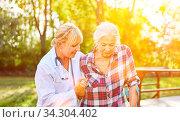 Alte Frau mit Gehhilfe und Physiotherapeutin bei Bewegungstherapie im Sommer im Garten. Стоковое фото, фотограф Zoonar.com/Robert Kneschke / age Fotostock / Фотобанк Лори