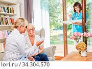 Ärztin kontrolliert den Blutdruck bei einer Seniorin in ihrer Seniorenwohnung. Стоковое фото, фотограф Zoonar.com/Robert Kneschke / age Fotostock / Фотобанк Лори