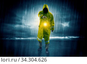 Raincoated man walking in storm with glowing lantern in his hand. Стоковое фото, фотограф Zoonar.com/rancz / easy Fotostock / Фотобанк Лори