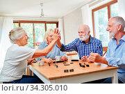 Senioren geben sich ein High Five beim Domino spielen in einem Wettkampf. Стоковое фото, фотограф Zoonar.com/Robert Kneschke / age Fotostock / Фотобанк Лори