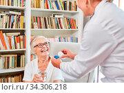 Altenpflegerin oder Krankenschwester gibt Seniorin im Altenheim ihr Medikament. Стоковое фото, фотограф Zoonar.com/Robert Kneschke / age Fotostock / Фотобанк Лори