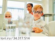 Schlauer Junge als Schüler oder Trainee in einer Klasse oder in einem Meeting. Стоковое фото, фотограф Zoonar.com/Robert Kneschke / age Fotostock / Фотобанк Лори